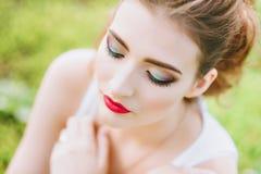 Mujer con el lápiz labial rojo y maquillaje coloreado, retrato en naturaleza Mirada de la cámara Fotos de archivo libres de regalías