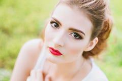 Mujer con el lápiz labial rojo y maquillaje coloreado, retrato en naturaleza Mirada de la cámara Foto de archivo libre de regalías