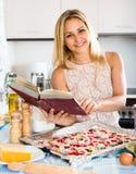 Mujer con el libro de cocina que cocina la pizza Foto de archivo