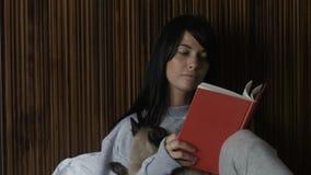 Mujer con el libro de lectura del gato metrajes