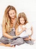 Mujer con el libro de lectura del niño Fotos de archivo libres de regalías
