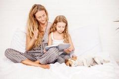 Mujer con el libro de lectura del niño Fotografía de archivo libre de regalías