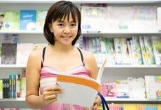 Mujer con el libro en manos en una librería imagenes de archivo