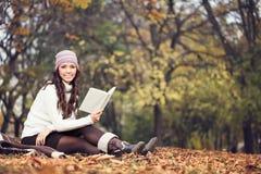 Mujer con el libro en parque del otoño Fotografía de archivo