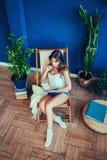 Mujer con el libro que se sienta en silla Fotos de archivo libres de regalías