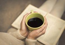 Mujer con el libro viejo y la taza de café Imagen de archivo