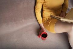 Mujer con el libro viejo y la taza de café Fotografía de archivo libre de regalías