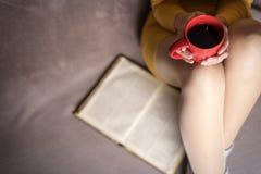Mujer con el libro viejo y la taza de café Imagenes de archivo