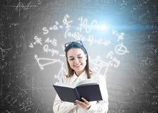 Mujer con el libro y fórmulas en la pizarra Fotos de archivo libres de regalías