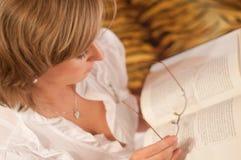mujer con el libro y los vidrios Foto de archivo libre de regalías