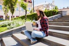 Mujer con el limonade que se sienta en las escaleras de la ciudad y que usa el ordenador portátil Imágenes de archivo libres de regalías