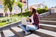 Mujer con el limonade que se sienta en las escaleras de la ciudad y que usa el ordenador portátil Foto de archivo libre de regalías