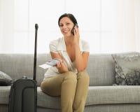 Mujer con el móvil de discurso del billete del pasaporte y de avión Fotos de archivo