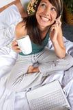 Mujer con el móvil en cama Foto de archivo