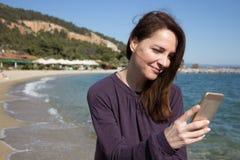 Mujer con el móvil en la playa Imagenes de archivo