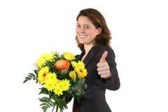 Mujer con el manojo de flores que presentan con los pulgares para arriba Foto de archivo