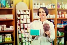 Mujer con el manojo de hierbas secadas en droguería Imágenes de archivo libres de regalías
