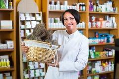 Mujer con el manojo de hierbas secadas en droguería Foto de archivo libre de regalías