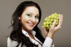 Mujer con el manojo de uvas imagenes de archivo