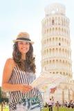 Mujer con el mapa delante de la torre inclinada de Pisa Foto de archivo libre de regalías