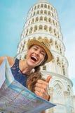 Mujer con el mapa delante de la torre inclinada de Pisa Imágenes de archivo libres de regalías