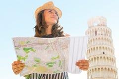 Mujer con el mapa delante de la torre inclinada de Pisa Imagen de archivo libre de regalías