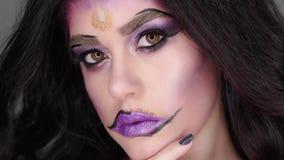 Mujer con el maquillaje hermoso que presenta en cámara Ella tiene un rasgón metrajes