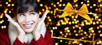 Mujer con el marco de caja de la Navidad en luces de oro Fotos de archivo libres de regalías