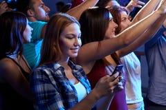 Mujer con el mensaje que manda un SMS del smartphone en el concierto Fotos de archivo