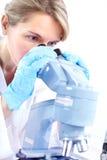Mujer con el microscopio Fotografía de archivo libre de regalías