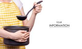 Mujer con el modelo de la cucharón y del cazo de la cocina del delantal a disposición imagen de archivo libre de regalías