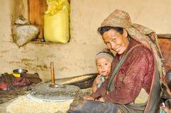 Mujer con el molino del grano en Nepal Imagenes de archivo