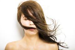 Mujer con el movimiento del pelo en el fondo blanco Foto de archivo