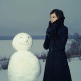 Mujer con el muñeco de nieve Imagen de archivo