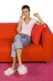 Mujer con el móvil en el sofá Imágenes de archivo libres de regalías