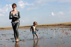 Mujer con el niño en fango curativo imagen de archivo