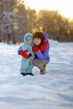 Mujer con el niño pequeño en el parque del invierno Fotos de archivo libres de regalías