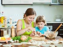 Mujer con el niño que cocina el pelmeni de los pescados (pelmeni), siempre junto fotos de archivo libres de regalías