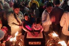 Mujer con el niño que dona el dinero en la ceremonia de Ganga Aarti en el ashram de Parmarth Niketan en la puesta del sol Foto de archivo