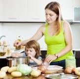 Mujer con el niño que hace la sopa Imágenes de archivo libres de regalías