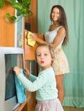 Mujer con el niño que limpia en casa Foto de archivo libre de regalías
