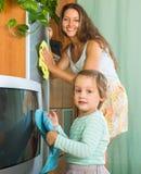 Mujer con el niño que limpia en casa Imágenes de archivo libres de regalías