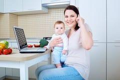 Mujer con el niño que prepara la comida y que habla en el teléfono Foto de archivo libre de regalías