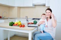 Mujer con el niño que prepara la comida y que habla en el teléfono F feliz Fotografía de archivo libre de regalías