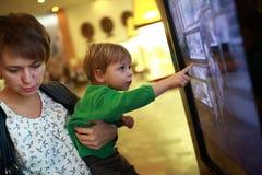 Mujer con el niño que usa la pantalla táctil Imagenes de archivo