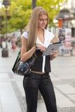 Mujer con el ordenador de la tablilla del ipad en la calle Fotografía de archivo