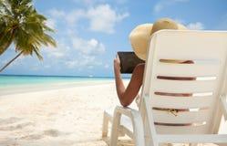 Mujer con el ordenador de la tablilla en la playa Fotografía de archivo