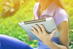 Mujer con el ordenador de la tablilla en parque Imagenes de archivo