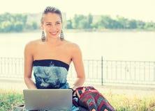 Mujer con el ordenador portátil al aire libre en un parque imágenes de archivo libres de regalías