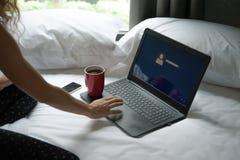 Mujer con el ordenador portátil, el teléfono móvil y una taza de café en la cama Fotos de archivo libres de regalías